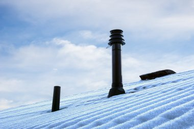 Roof with ventilation pipe and flue terminal in winter