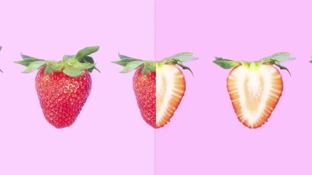 Zastavit animaci pohybu. Zralé šťavnaté červené celé jahody se zelení pohybující se podél linie mění v půli na růžovém pozadí