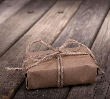 Small brown package wrapped with string on old wood boards stock vector