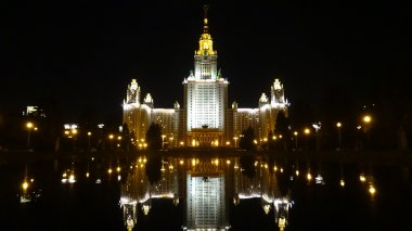 The building of Moscow State University at night. Reflection in the park pond. Footage of educational complex buildings (MSU). Moscow State University named Lomonosov. Russia, Moscow. Stalinist Empire style or Socialist Classicism.