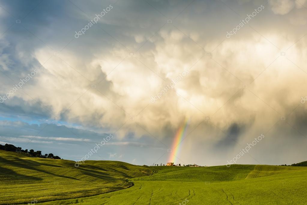 Regenboog boven het veld na een voorjaar regen storm u stockfoto