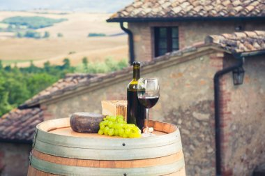 Red wine, pecorino cheese on a wooden barrel in the background of the Tuscan landscape, Italy stock vector