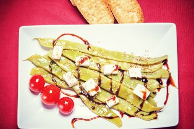 A plate of string beans with feta cheese and sesame seeds, decor