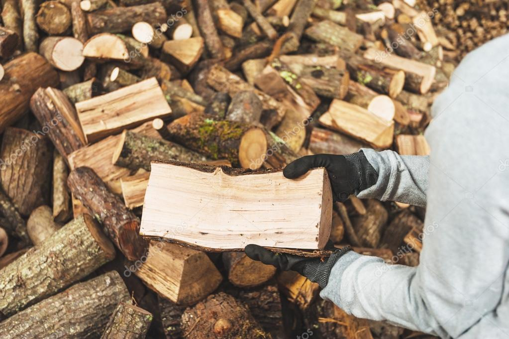 Firewood in a piece of wood stored on the stack, hands holding a