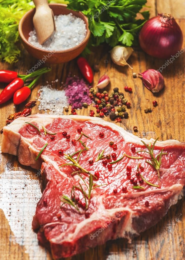 Close-up of fresh meat steak with spices on wooden background