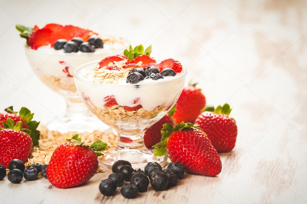 Strawberries, blueberries and breakfast cereal in yogurt on a wo