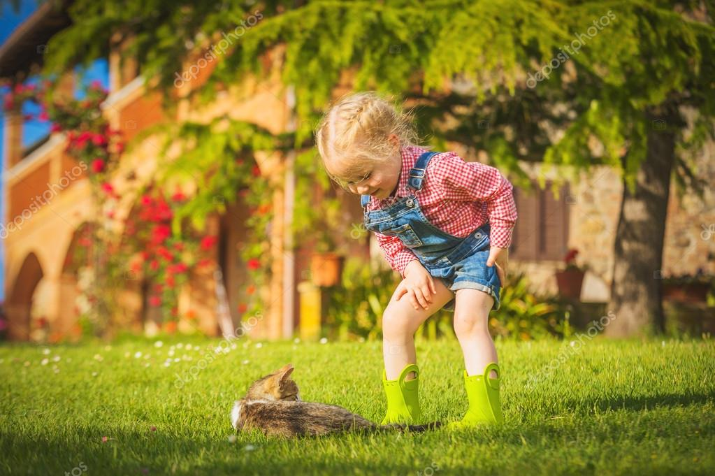 Little Girl and cat play on a green meadow in spring beautiful d