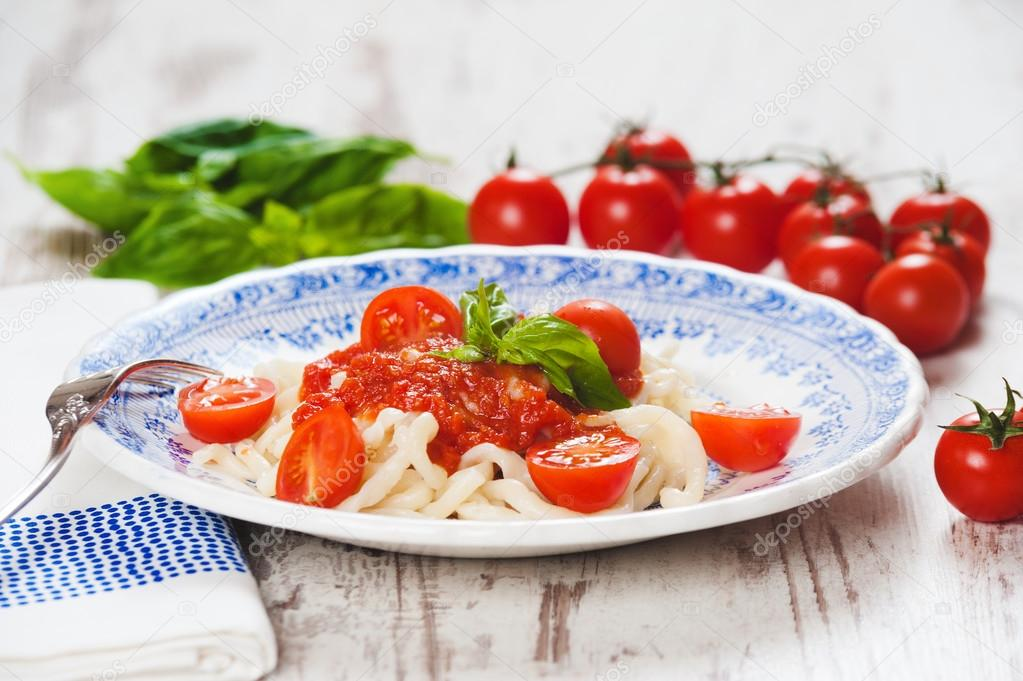 Healthy plate of Italian spaghetti topped with a tasty tomato an