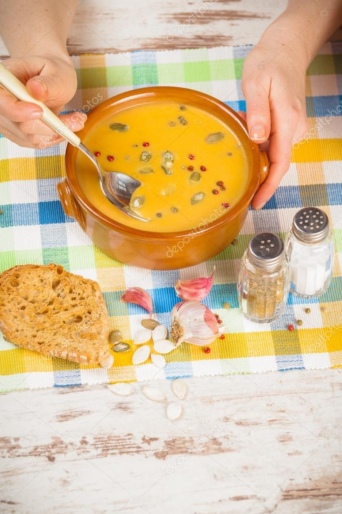 Homemade pumpkin soup and hands with a spoon on rustic table
