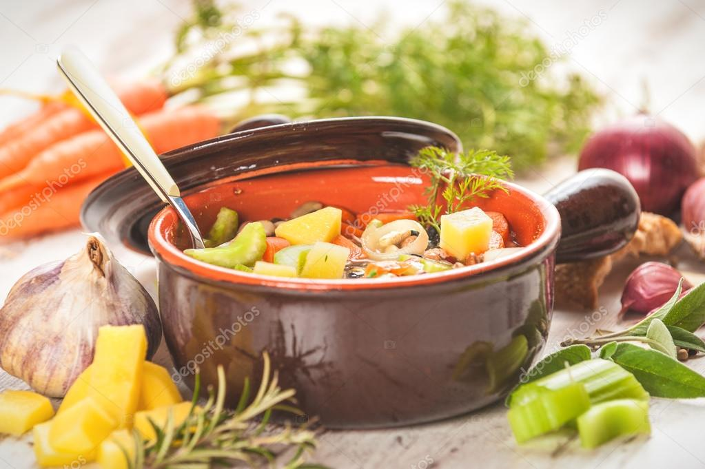 Rural vegetarian broth soup with colorful vegetables and rustic
