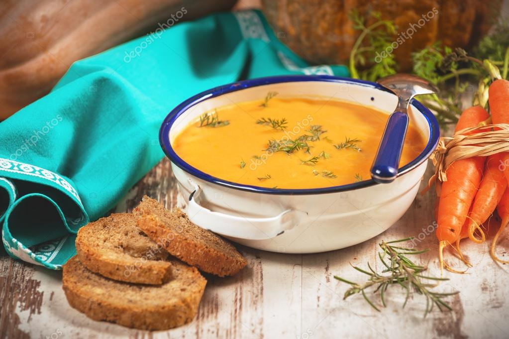 Pumpkin soup with bread crouton on white wood table