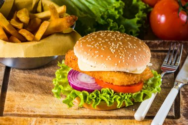 Country-style dish on a wooden table with a chicken burger and f