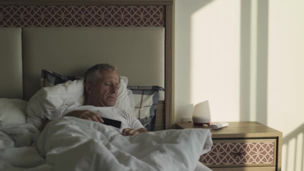 An elderly man sleeps in bed in the early morning.