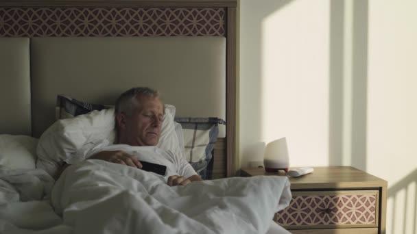 Starší muž spí brzy ráno v posteli..