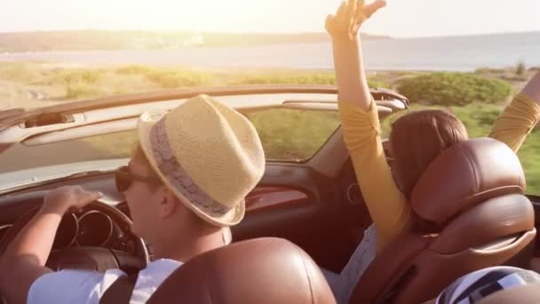 Cute Young Couple Driving At Sea Front Woman Enjoying Waiving Arms In The Air In Convertible Car Wind Blowing Hair Summer Fun Vacation Adventure Concept