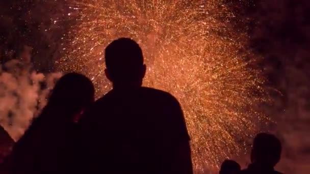 Férfi és nő sziluettek élvezi a gyönyörű tűzijáték Show szilveszteri negyedik július romantikus dátum évforduló koncepció