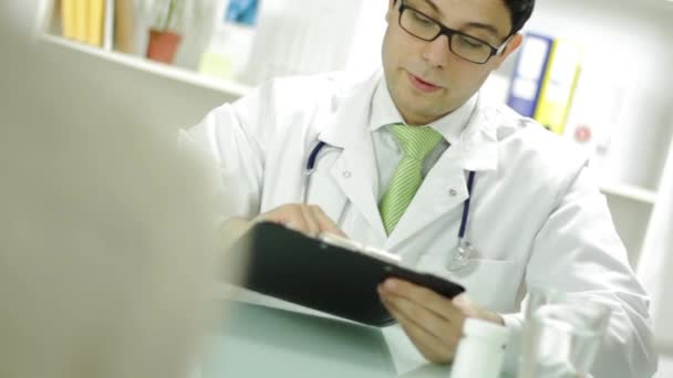 Medical Doctor Checking Patient Records and Offering Pills