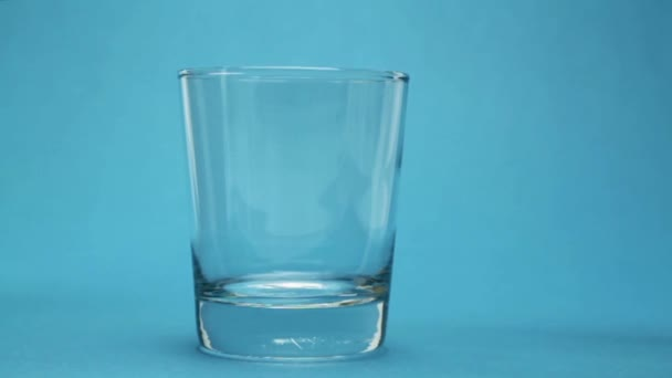 Tekoucí voda ve skle modré pozadí
