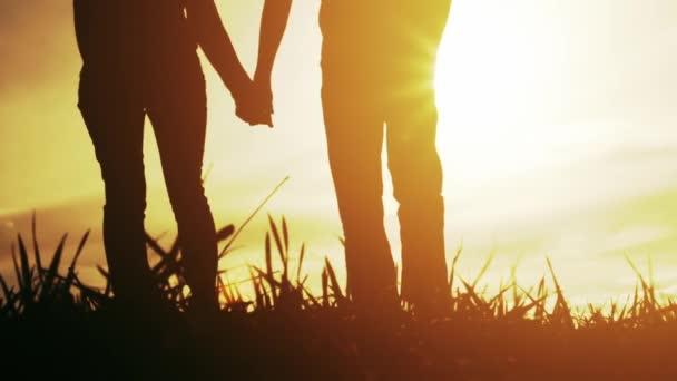 Young Couple Man Woman Walking Toward Sunset Silhouettes