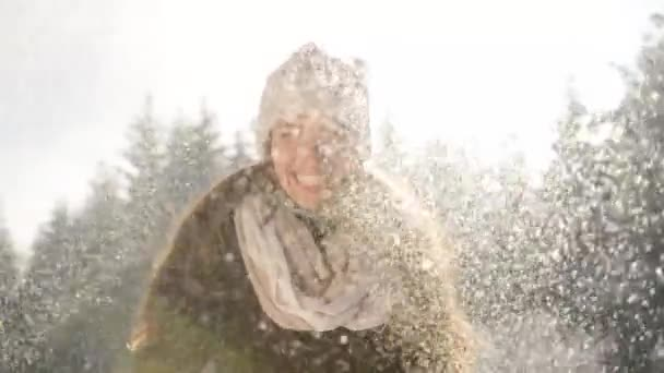 Pretty young woman play with snow