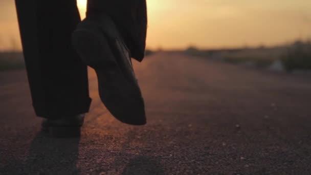Man walking away on the road on sunset