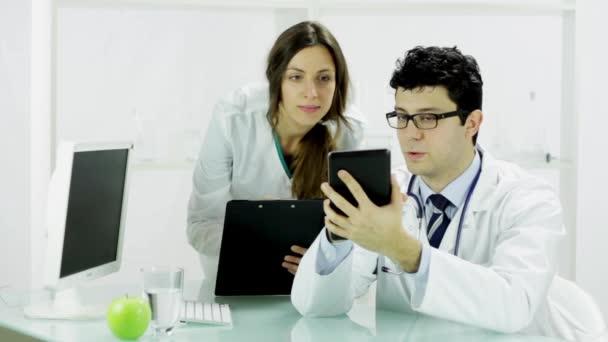 Doctor showing female nurse tablet PC