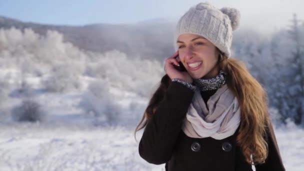 Žena s mobilním telefonem v lese sněhu