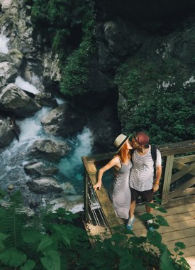 Hipster couple hiking on the background of a mountain river