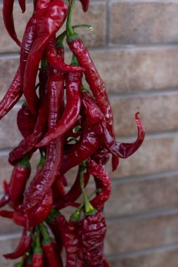 Background image. A bunch of red hot chili peppers on a brick wall background