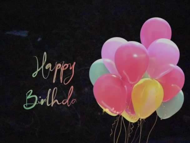 Balloons and Happy Birthday reveal text, balloons move in breeze as Happy Birthday is rainbow magic writing on black background loop animation for virtual card