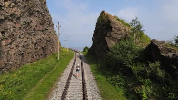 4K The drone flight follows a female traveler with a backpack walking along the railway tracks laid between the rocks. A sunny summer day, a great day for hiking. Local travel and weekend hikes.