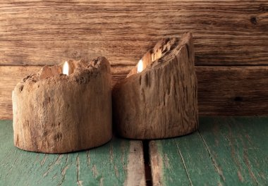 Two candles placed in very old wooden bars on green board