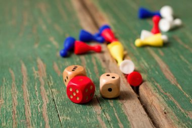 Few dices and color figurines on green wooden board