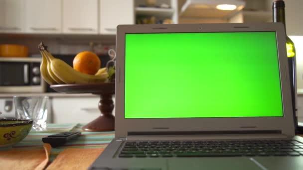 Laptop-val zöld képernyő a konyhaasztalon