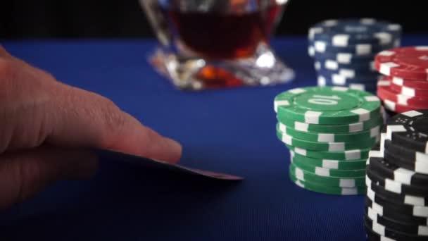 Dvě esa v ruce a Gambling žetony v kasinu modrý filc