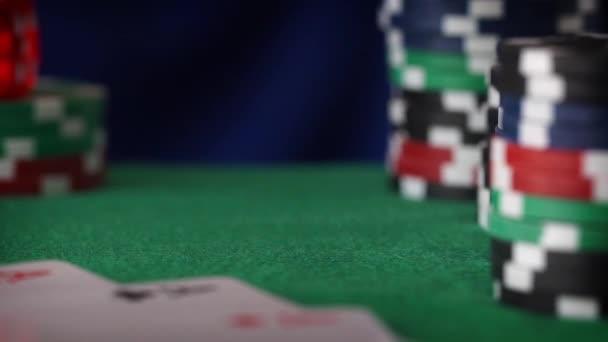 Dvě červené kostky rohlíky v ruce, kasinové žetony, karty na zelené plsti