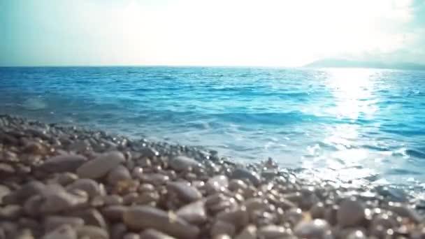 Moře, Peebleovou břehu a vlny. Přímořská krajina při západu slunce.