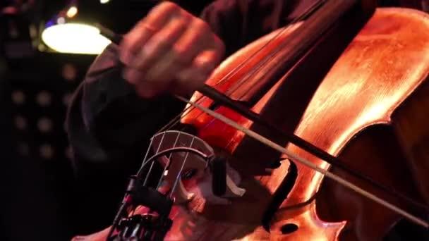 Koncert, egy ember, a cselló, játszott kéz közelről