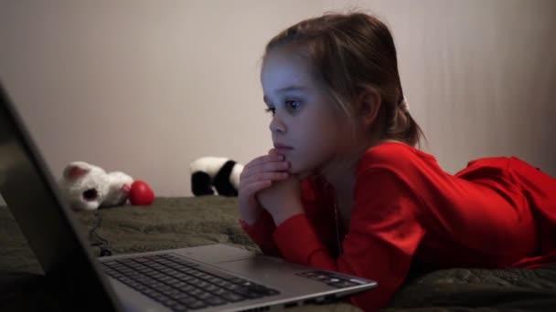 Little girl at night watching cartoons at computer.