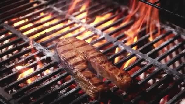 A lédús lazac steak csíkokkal grillezésre kerül egy grillsütőn a tűz és a füst lángjában. Tengeri herkentyűk a grillen. tengeri herkentyűket főz faszén grillen a pikniken és a grillsütésen. Ételt készítek a táborban.
