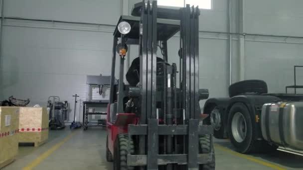 Samec mechanik jezdí se skladovým nakladačem přes opravnu. Přeprava náhradních dílů pro automobily na čerpací stanici na vysokozdvižném vozíku. Provozovatel nakladače pracuje v logistice autoservisu