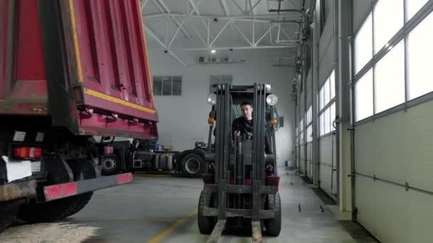 Provozní mechanik projíždí na skladovém nakladači velkou opravárenskou dílnou. Přeprava náhradních dílů pro automobily na čerpací stanici na vysokozdvižném vozíku. obsluha nakladače pracuje v logistice autoopravny