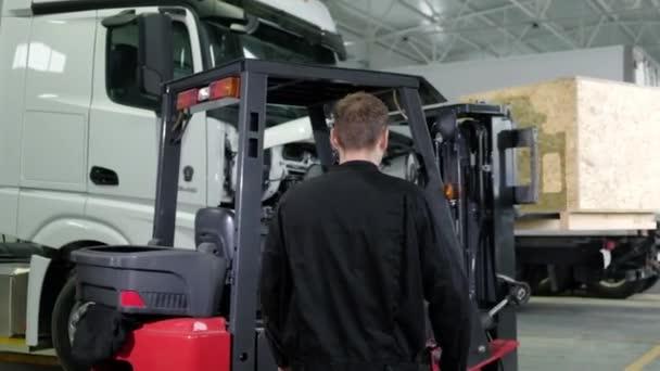 Mechanik pracuje na skladovém nakladači ve velké opravně. Přeprava náhradních dílů pro osobní automobily na čerpacích stanicích vysokozdvižného vozíku. obsluha nakladače pracuje v opravně logistických automobilů
