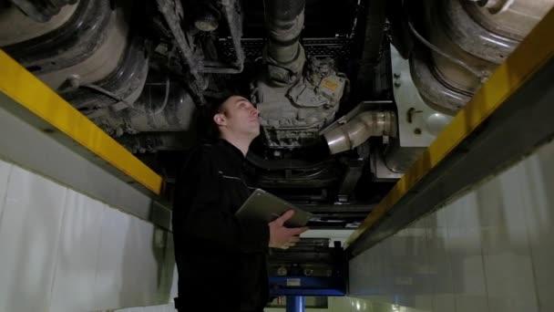 Automechanik provádí kontrolu nákladního auta na čerpací stanici. inspektor zaznamenává všechny poruchy a problémy s autem v tabletu. Autoservis a opravy automobilů. inženýr pracuje pod zvedacím strojem