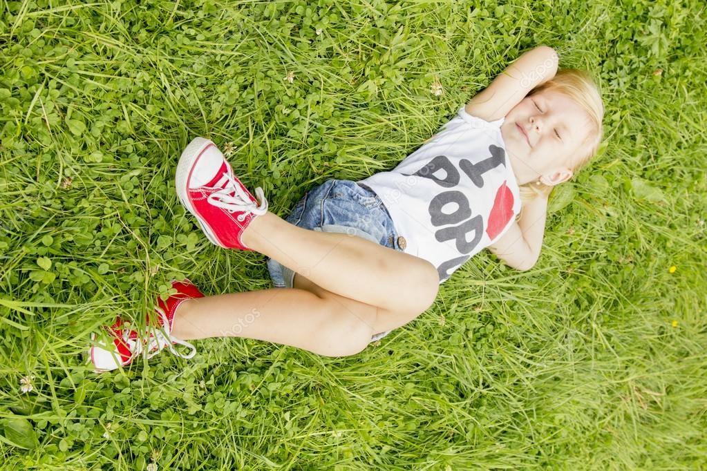 little girl lying on the grass and dreaming