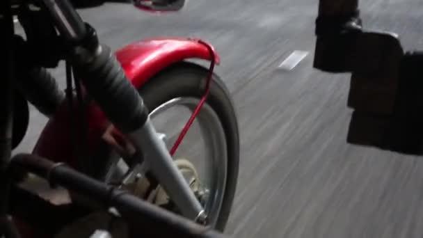 Motorkářka jezdí na motorce. Pohled zdola nohou kožené boty. Zaměřit se na zadní kolo