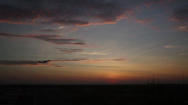 osobní letadlo letět nahoru nad vzletovou dráhu letiště při západu slunce