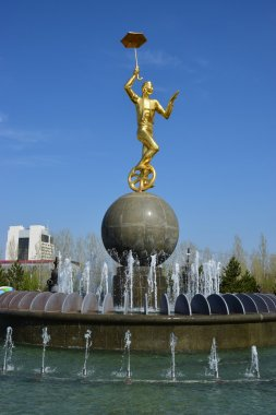 Gilded statue of a circus man on a monocycle in Astana