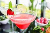 eine Mischung aus zwei erfrischenden Cocktails: Limetten-Daiquiri und Erdbeer-Daiquiri auf einem Tisch in einem Restaurant mit kreativer Salzdekoration am Rand des Glases mit frischer Minze und Limettenscheiben