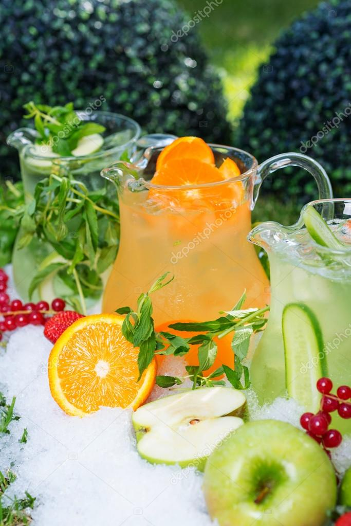 a mix of several bright colored delicious cold lemonade carafes of cucumber and orange and basilon with creative composition of ice berries oranges apples and mint. soft focus